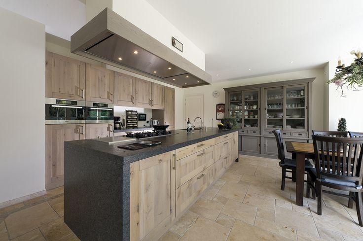 Robuuste houten keuken met kookeiland. Deze robuuste houten keuken is volledig handgemaakt met een goed oog voor detail. Kijk bijvoorbeeld eens naar de houten ombouw  boven de schouw van het eiland. Ook de plavuizen passen perfect in het plaatje van deze robuuste maar moderne landelijke keuken. Tieleman
