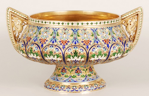 """A Russian silver gilt and cloisonne enamel 2 handled punch bowl on a circular pedestal base, workmaster Antip Kuzmichev, stamped """"Made for Tiffany and Co""""., Moscow, late 19th century. Enameled with polychrome roundels and scrolling foliate motifs against a gilt ground. The pointed handles pierced with fanciful birds."""