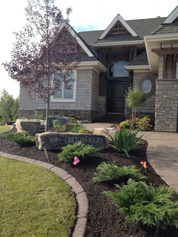 FrontScaping / This picture shows a home where the foundation bed was extended to include the driveway. Care was taken to choose plants that would stay short and narrow in height and width, but were substantial enough to make a presence. The driveway garden allowed the homeowners to install a custom address boulder-a very nice touch for this home.