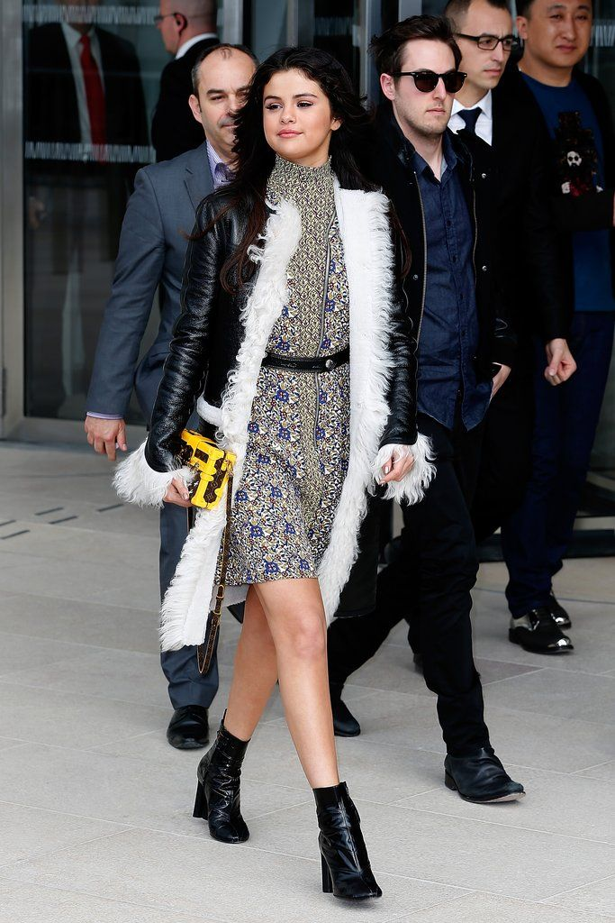 Selena wore this feather-trimmed leather jacket over a printed dress when she arrived at the Louis Vuitton ...