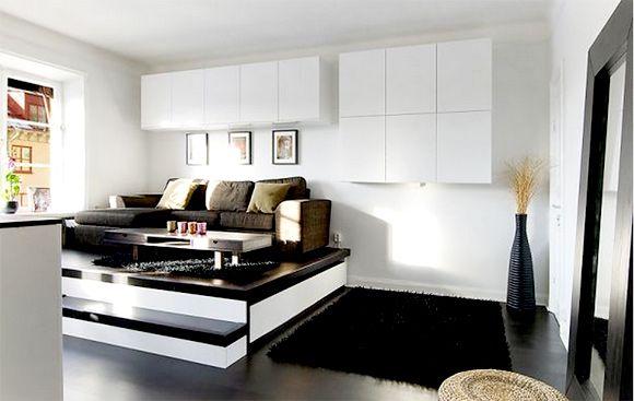 Sala de estar de pequeno apartamento foi projetada com plataforma para separar ambiente e guardar a cama durante o dia dentro do tablado (Foto:  Homedit)