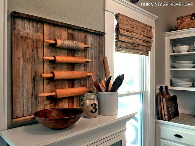 love the collection of rolling pins. She used door stoppers (spray painted) to hang them! Backed on the barn board = perfect