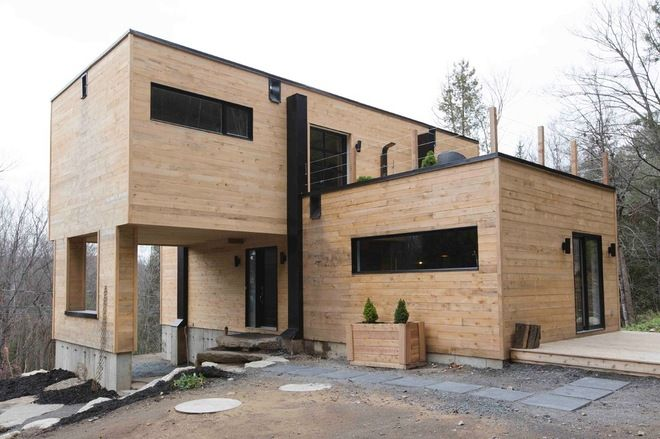 They clad the exterior in unstained hemlock spruce, because Dubreuil didn't want to paint her house every year. - Each shipping container is each 8 feet by 40 feet. Two are connected on the first floor, and two on the second are as well, forming a cross shape.