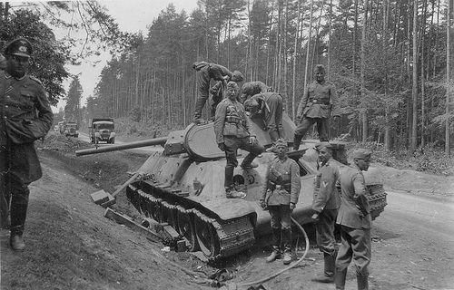 Soviet T-34   1941  German soldiers inspect an abandoned Soviet tank T-34