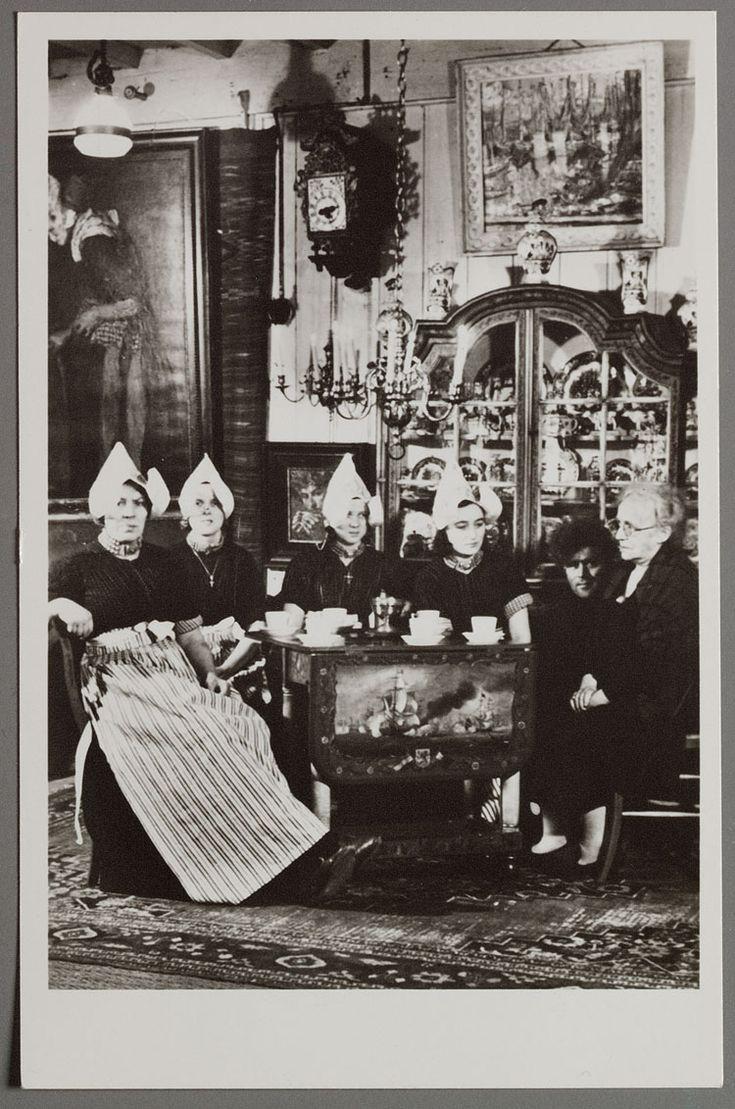 Interieur HOTEL SPAANDER Volendam. Tel. 204-205. 1950-1960 Vijf Volendamse vrouwen poseren om een beschilderd klaptafel in Hotel Spaander: Maart van Vlaanderen (Pan), Aaf Steur, Lijstje Steur (Drum), Aal Stroek (Rus), Evert Veerman (Seek) en Alida Spaander op de thee. De vier vrouwen links zijn in werkjak. Een pronkkast op de achtergrond. #NoordHolland #Volendam