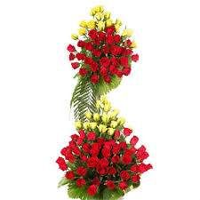 Dedicated affection is a tall arrangement of yellow and red roses.