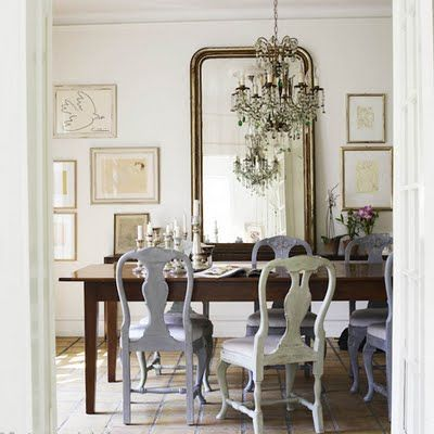 This vertical antique mirror has two functions- it's not only a beautiful addition to this playful dining room, which mixes a traditional wood table, ceiling light and pastel painted chairs, but it also helps the space appear bigger.