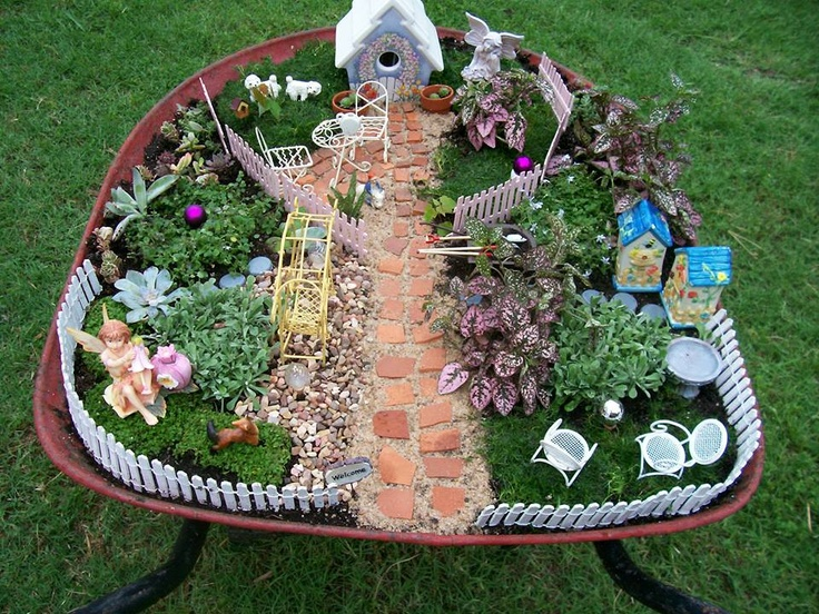 I'm officially obsessed with fairy gardens. This one is in an old wheelbarrow that belonged to my grandfather. Lots going on here. The walkway is pieces of a broken flower pot. The gazing ball is a mini ornament on a golf tee. The stepping stones are bottle caps painted grey. The pink fence is small craft sticks glued together and painted.