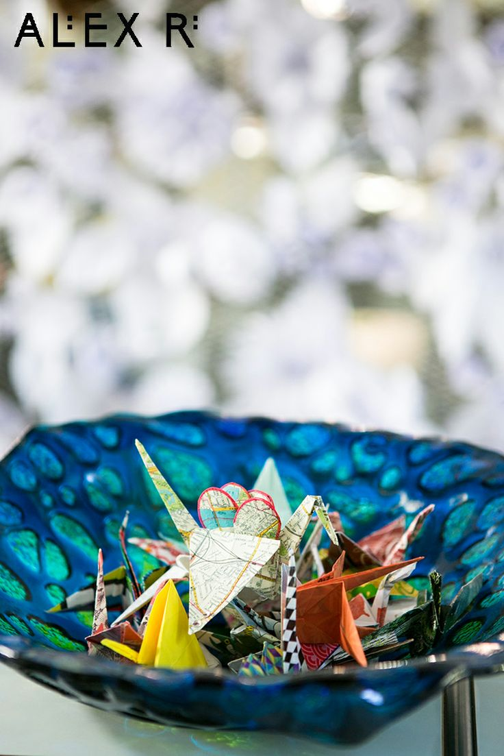 Colourful wedding: paper cranes in a glass bowl with a curtain of white paper flowers behind