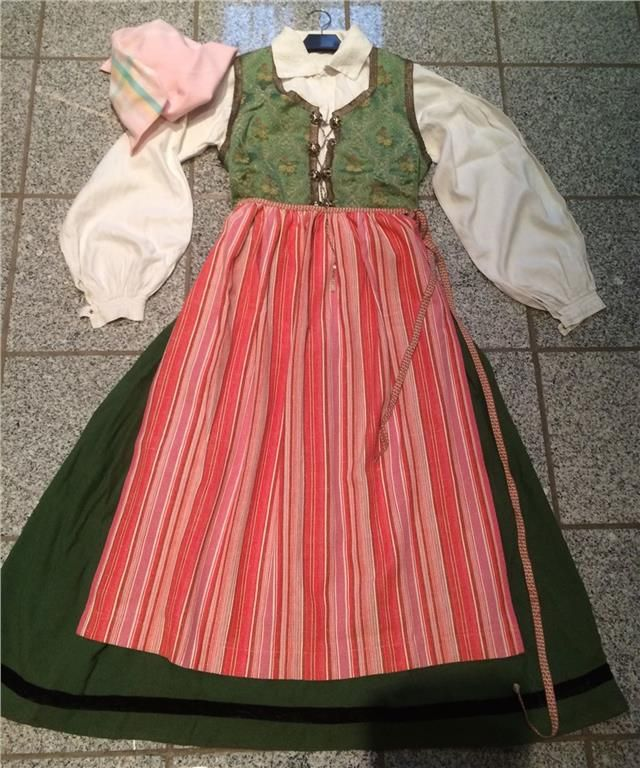 Skåne county costume. Bodice: silk brocade w silver ribbon. 8 silver hooks with a silver chain. Woolen skirt. Linen blouse w embroidery & plenty of pleats at the shoulders. Apron in cotton with beautiful ribbon. Cotton headscarf. Bust 90 cm. Waist 78 cm (these can be adjusted with the laces). Height 132 cm (can be extended 4 cm). Apron is 82 cm. 1/5