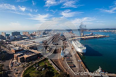 Colorful photo image high elevation overlooking Durban harbor east coast South-Africa. Looking east at harbor entrance beach buildings and large car vehicle export import terminal, ships railway lines infrastructure.