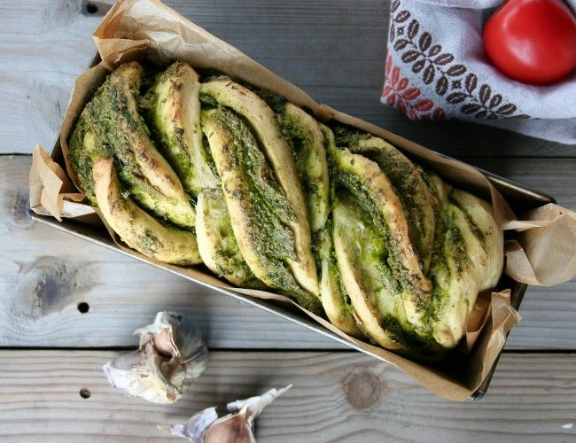 Chléb se špenátovo-bylinkovým pestem, krok 4: Těsto vyválejte na plát cca 30 x 35 cm. Potřete pestem a stočte na délku do rolády. Spoj nechte vespod a zvrchu rozkrojte napůl po celé délce. Stočte části do copu. Přesuňte do chlebíčkové formy vyložené pečícím papírem.