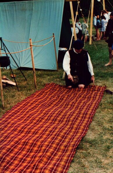 """A Demo of the """"whole nine yards"""" Where they take nine yards of tartan, pleat it by hand, belt it and wear it, with enough left over for over the shoulder fly plaid. This was how it was done back in the day, for real."""