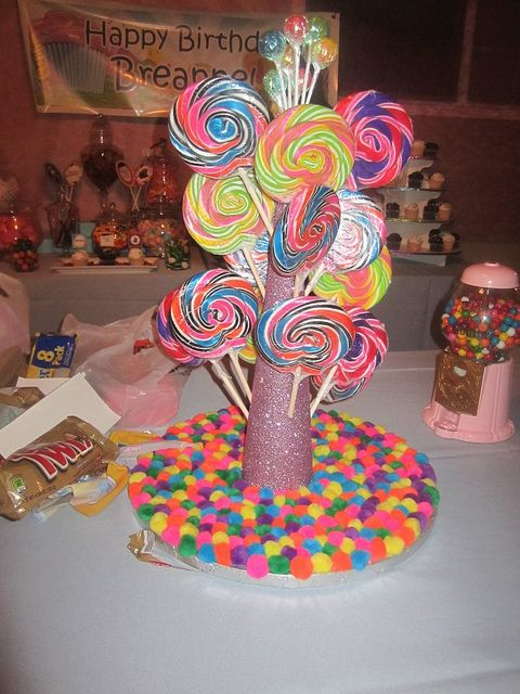 Lollipop Centerpiece - I adore this centerpiece. You can find all these supplies at Michaels. I bought a cake board and hot glued each of these little pom-poms to it.  I bought a huge styrofoam cone, hot glued it to the board, and painted the whole thing in glue so I could COVER it with glitter.  Once it was dry, I started putting the lollipops in the styrofoam cone, alternating sides so it would stay balanced.  I topped it off with a mini bunch of lollipops I purchased at our local candy…
