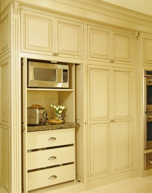 Appliance storage built into tall cabinet with pocket doors. That way everything is hidden, yet accessible.