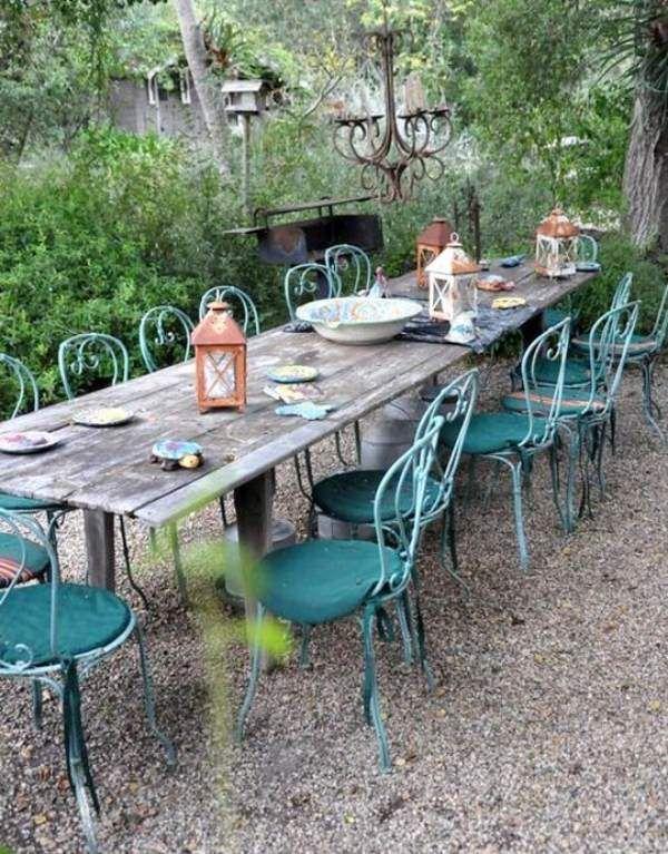 table en bois rustique et chaises métalliques bleues dans le jardin