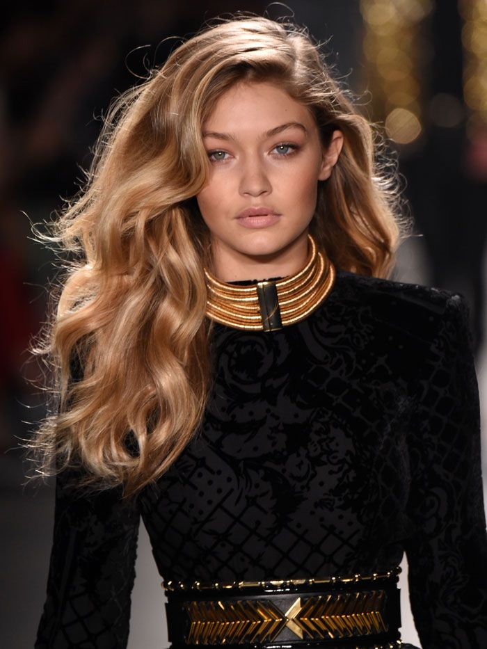 Gigi Hadid wears a black and metallic H&M Balmain ensemble.