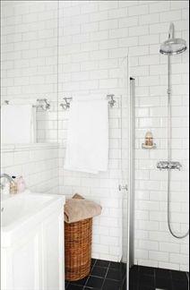 Badrummet är inrett med fasetterat kakel. En infälld spegel täcker väggen ovanför handfatet vilket ger en känsla av rymd. På golvet gråsvart klinker. Vitt skåp och handfat från Ikea, kranar, duschvägg och duscharmatur från Fredells.