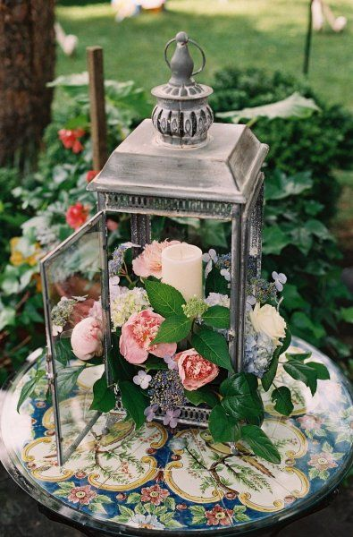 Lantern filled with flowers and candle.