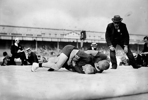 A referee closely watches the final of the light heavyweight Greco-Roman wrestling event. Verner Weckman of Finland won the gold medal, beating fellow countryman Yrjo Saarela.   - 1908 Olympic Games in London