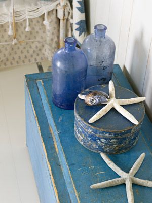 Little Vignettes-   In this photo: A document box from the late 19th century now serves as a trunk for extra blankets in a guest bedroom. Old pharmacy bottles and a Shaker box echo the blue hue.