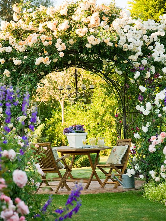 An arbor becomes a backdrop for a bounty of blooms. A deep arbor offers enough room to shelter a small table and chairs. With plenty of screened space from above, pavers define a section underneath the structure. Romance comes courtesy of elegant accents, including this delicate, detailed candlelit fixture. A profusion of climbing roses blooms from every angle; choose plants that will offer robust growth and vigorous flower patterns. Hide the base of an arbor with a flowering groundcover or…