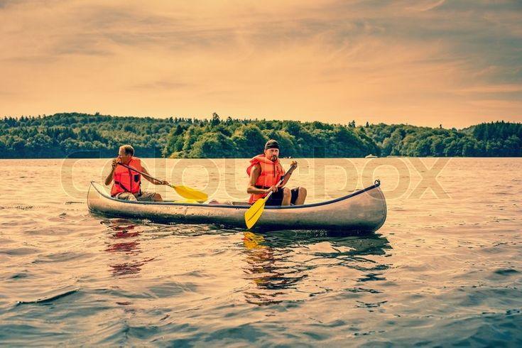 Stock image of 'Men sailing a canoe wearing orange lifejackets'