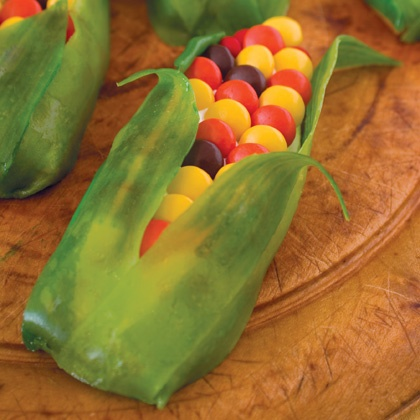 fruit leather or fruit roll-ups for the husks and m & m's for the corn. Instead of cookies you could also use a graham cracker or rice krispy treats shaped the way you needed with icing to hold the M's.