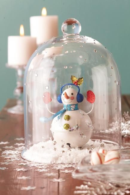 Transform a cloche into a snow globe with a few crafts materials. Set a snowman ornament on a layer of fluffy snow. Cover with a bell-shape cloche embellished with rhinestone gems. Scatter snowflake confetti to complete the arrangement.