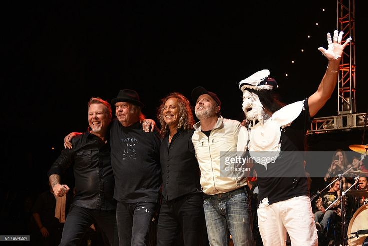 Neil Young poses onstage with Robert Trujillo (Right, birthday cake on face) and the other members of the band Metallica, James Hetfield, Lars Ulrich, Kirk Hammett and Robert Trujillo during the 30th Anniversary Bridge School Benefit Concert at Shoreline Amphitheatre on October 23, 2016 in Mountain View, California.