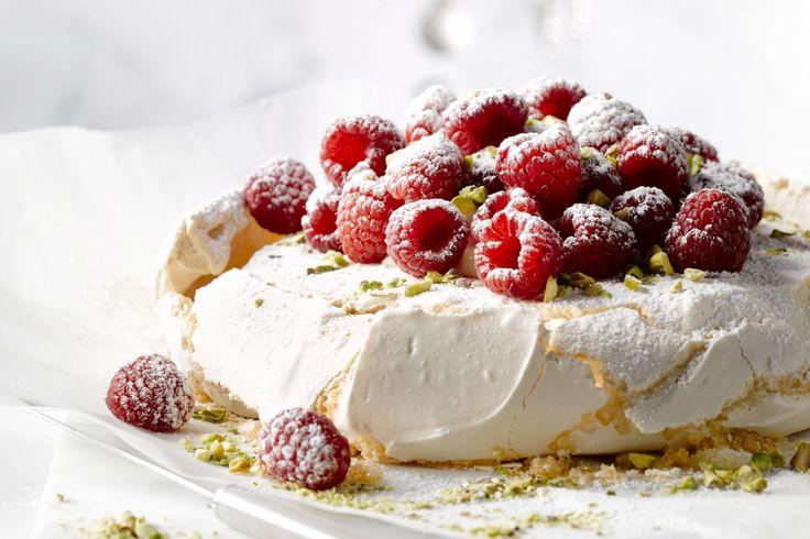 Deze sneeuwwitte pavlova afgewerkt met frambozen is ideaal voor de feestdagen. Dit dessert is een taart van meringue die dus lekker zoet smaakt. Verwe...