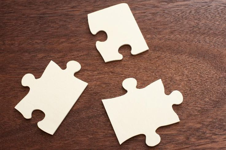 Close up of three blank jigsaw puzzle pieces placed in a triangle shape on a…