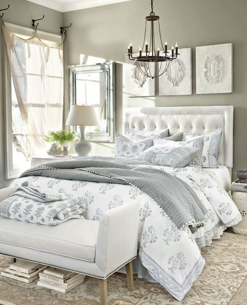 Neutral gray bedroom with white tufted headboard, triptych of prints above bed and bench at the foot of the bed