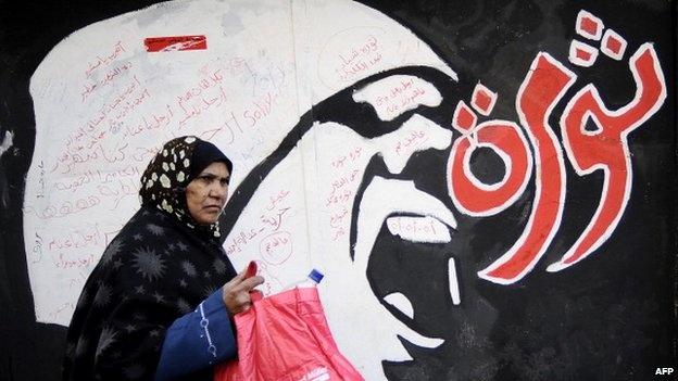 A woman walks past graffiti which reads revolution