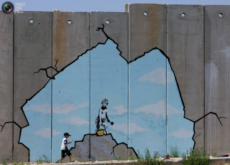 A Palestinian boy walks past a drawing by British graffiti artist Banksy near the Kalandia checkpoint in the West Bank.  August 10, 2005.