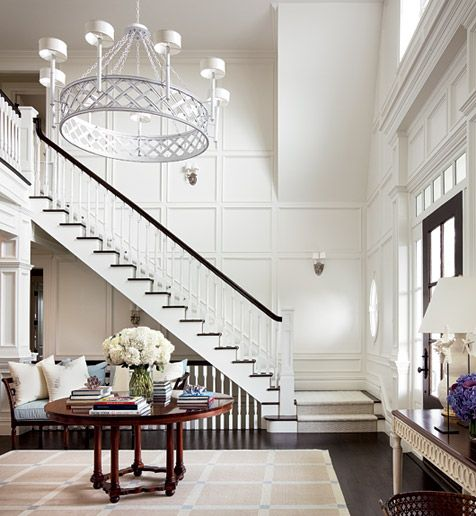 Foyer with a white chandelier, white paneled walls, a white staircase with black railing and steps, dark wood floor, a tan rug and a round wood table
