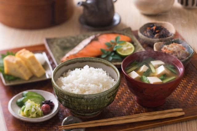 A traditional Japanese breakfast is a complete meal with rice, soup, vegetables, protein such as fish, and other side dishes to create a meal equivalent to lunch or dinner.