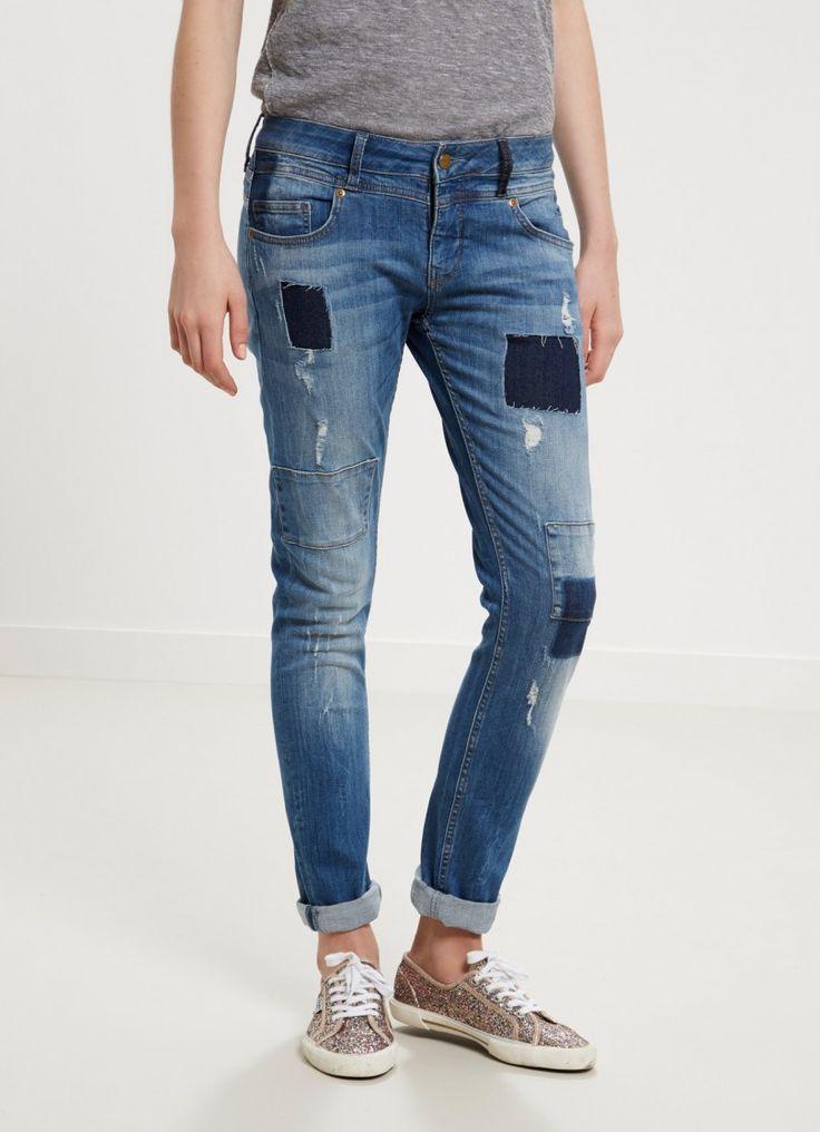 Jean de cintura regular y lavado medio. Cinco bolsillos ribeteados. Detalle de rotos de denim en la parte delantera. Vuelta en el bajo.