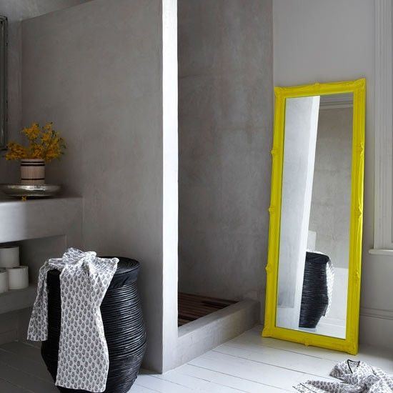 Showers don't have to be white and clinical. This luxurious shower room features a built-in shower unit which gives the room a wet room feel. A mirror, painted in a zesty lemon yellow, brings colour to the scheme, while chic accessories like the linen basket, add warmth and texture.