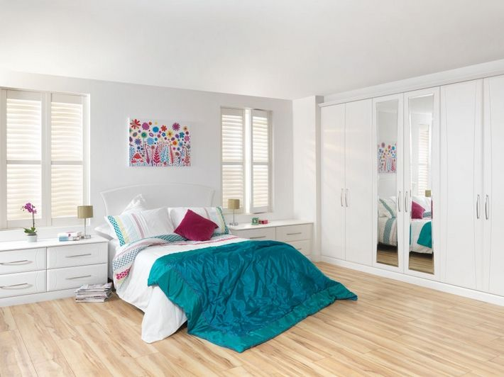 Reflect your bedroom's colorful design with these cool white doors and bevelled edged mirrors.