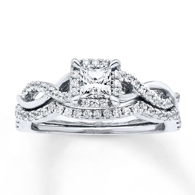 A princess-cut diamond is traced in round diamonds to form the brilliant center of her engagement ring in this pretty bridal set for her. The 14K white gold band features intertwining waves — one lined in additional round diamonds — while the matching wedding band is contoured and lined with round diamonds to complement. The bridal set has a total diamond weight of 3/4 carat. Diamond Total Carat Weight may range from .69 - .82 carats.