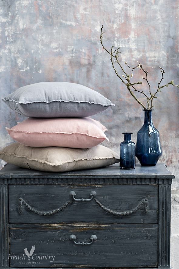 Soft moody blue bedroom furniture with smokey blue vases and natural linen cushions.