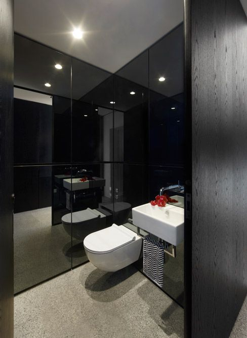 Powder room: tinted mirror wall panels, polished concrete floor, wall-hung toilet, wall-mounted basin with towel rail, black wooden joinery, downlights