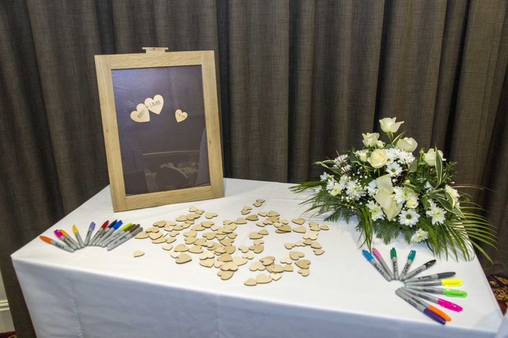 Write your name on a heart and throw it in a frame. Very nice idea and you can also hang it on a wall after your Wedding.