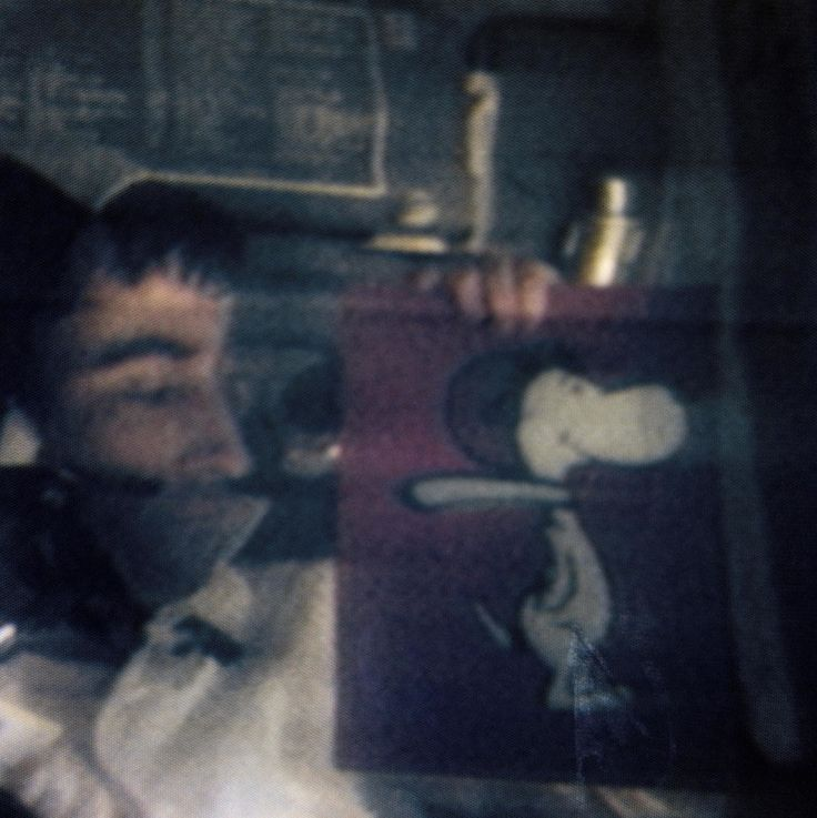 Astronaut John W. Young holds up a picture of Snoopy in an image from the Apollo 10 mission.