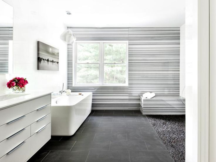 A floor-to-ceiling Marmara marble accent wall subtly steals the show in this modern master bathroom. The wall creates dramatic movement and interest without straying from the room's calm color palette of rich grays, soft blacks and crisp whites.