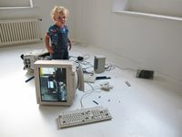 A blond toddler stands in a white room amid a mess of upturned, damaged computer equipment.