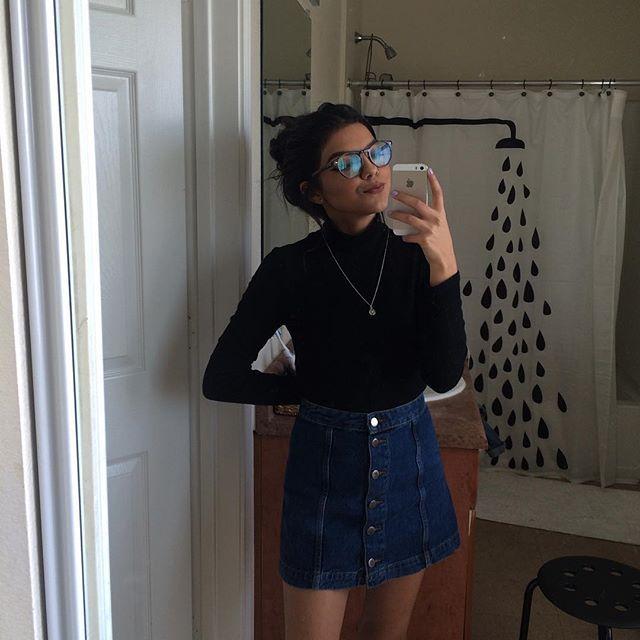 Black long sleeve turtleneck top, button skirt, glasses, necklace