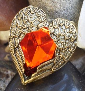 So beautiful!  A bright red gem sits amidst antique bronze metal wings.  The band is adjustable.  This ring is fashioned from mixed alloy metals.  Ring measures 2.5cm.