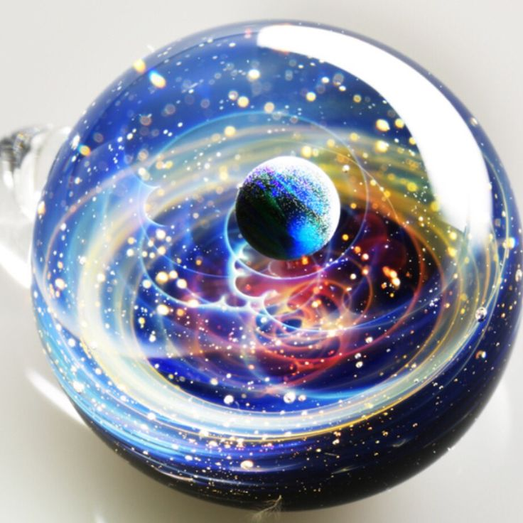 Glass artist Satoshi Tomizu sculpts small glass spheres that appear to contain entire solar systems and galaxies. Planets made of opals, flecks of real gold, and trails of colored glass seem to spin and loop like twists in the Milky Way. photographed here in a macro view